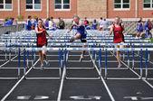 конкурировать в гонке с барьерами средней школы девочек-подростков — Стоковое фото