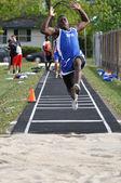 Мальчик подросток делает прыжок в длину в средней школы легкой атлетики встретиться — Стоковое фото