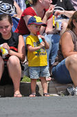 Oung Boy Eating a Frozen Treat While Watching Parade — Stock Photo