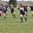 Player Running with the Ball in a Women's College Rugby Match - Lizenzfreies Foto