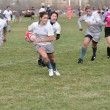 Player Running with the Ball in a Women's College Rugby Match - Stock Photo