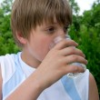 Young boy drinks water out of cups — Stock Photo