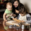 Mother and children making cookies — Stock Photo