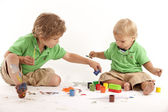 Siblings with paints and blocks — Stock Photo