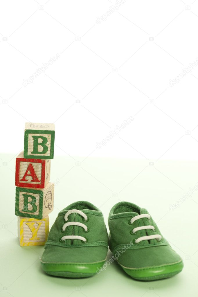 Green baby shoes and woddden blocks. Copy space  Stock Photo #8520423