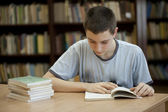 Young man in library — Stock Photo