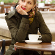 Beautiful woman drinking coffee in outdoor cafe — Stock Photo