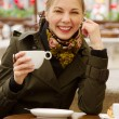 Beautiful woman drinking coffee in outdoor cafe — Stock Photo #10576603