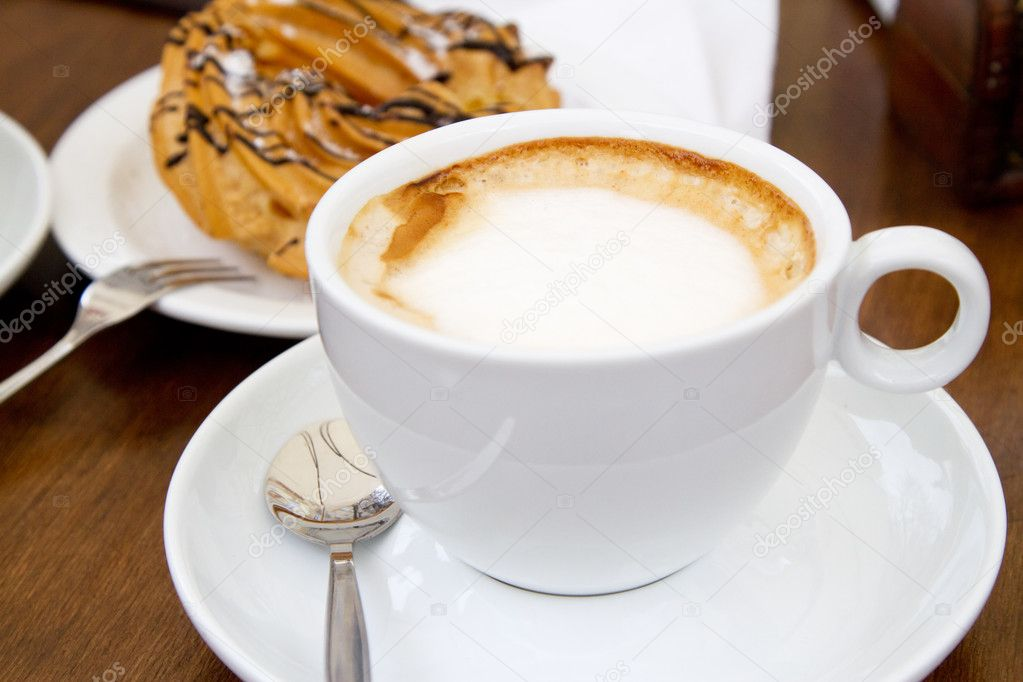 Cup of coffee on wooden table with cake on background  Stock Photo #10576610