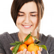 Young beautiful woman holding fresh tangerines — Stock Photo