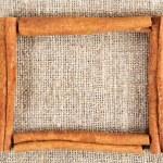 Cinnamon sticks frame on a sacking cloth — Stock Photo #8440033