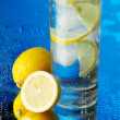 Glass of lemon ice water on blue background - Stock Photo