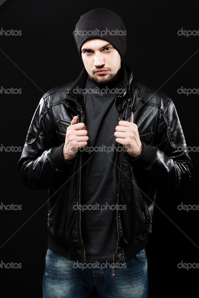 Handsome young man in black leather jacket, studio portrait  Stock Photo #8823894