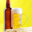 Beer mug and bottles on yellow background — Stock Photo