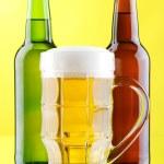 Beer mug and bottles on yellow background — Stock Photo