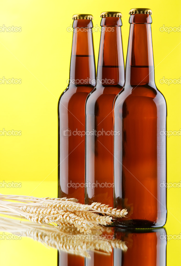 Beer mug and bottles on yellow background, studio photo — Stock Photo #9053776