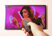 Remote control in man's hand and TV set — Stock Photo