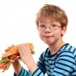 Stock Photo: Boy eating large sandwich
