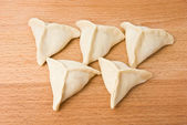 Triangular pelmeni on board — Stock Photo