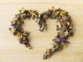 Heart of herbal tea with mountains herbs — Stock Photo