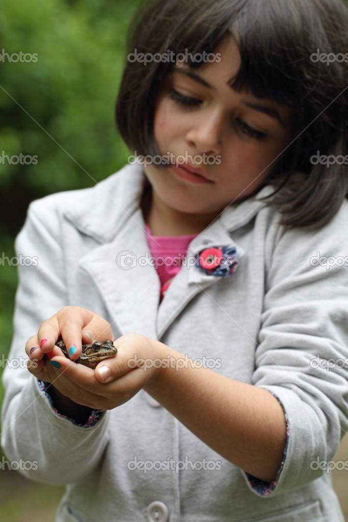 Details of a young girl holding a frog in his hands — Stock Photo #10666342
