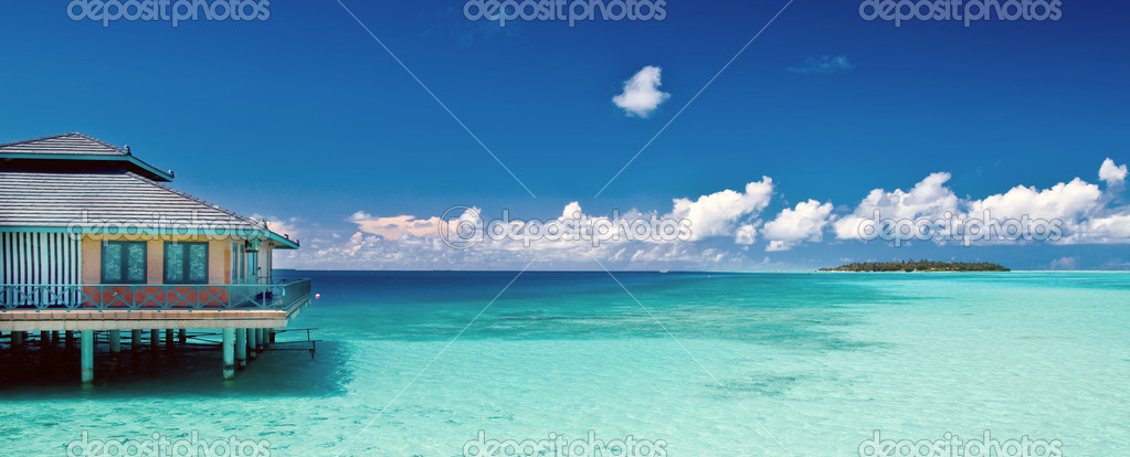 Tropical beach panorama with water hut and distant island on the maldives — Stock Photo #8636172