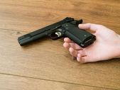 Black Pistol Gun in Dead Hand — Stock Photo