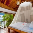 Stock Photo: Bedroom with canopy bed with sea view