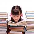 Stock Photo: Little gire reading book sitting among stacks of books