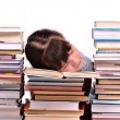 Little gire reading a book sleeping among stacks of books — Stock Photo