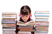 Little gire reading a book sitting among stacks of books — Stock Photo