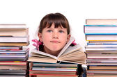 Portrait of cute girl sitting among stacks of books — Stock Photo