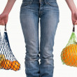 Close up of a woman with jeans carrying yellow fruits — Stock Photo
