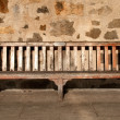 Wooden Park Bench with Memory Plate against a stone wall - Stock Photo