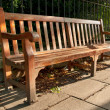 Wooden Park Bench with Memory Plate in the park shade - Stock Photo