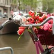 Basket of fresh bouquet of red tulips on bike — Foto de stock #8849349