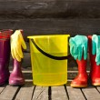 Bucket, rubber gloves and two pairs of rubber boots at wooden veranda — Stock Photo #8849940