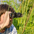 Man with binoculars in high grass — Stock Photo