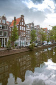 Amsterdam canals and typical houses with water reflections — Stock Photo