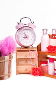Alarm clock and a lot of pink body care accessories isolated on white — Stock Photo