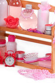 Cosmetic bottles and bath accessories arranged on a wooden shelf and alarm — Stock Photo