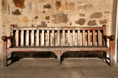 Wooden Park Bench with Memory Plate against a stone wall — Stock Photo