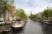 Typical Amsterdam's canal with and boats parked along it — 图库照片
