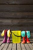 Two pairs of rubber boots, bucket and rubber gloves on sunny veranda — Stok fotoğraf