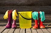Bucket, rubber gloves and two pairs of rubber boots at wooden veranda — Stock Photo