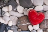 Red heart among pebble stones — Stock Photo