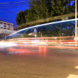 Light traces from moving cars at night - Stock Photo