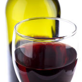 Glass of red wine with a wine bottle background — Stock Photo
