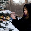 Girl decorating a fir tree - Stockfoto