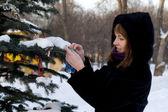 Girl decorating a fir tree — Stock Photo
